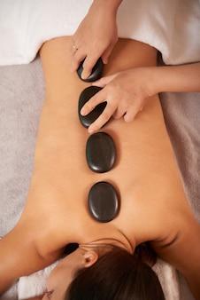 Mujer joven con masaje de terapia con piedras calientes en el salón de spa