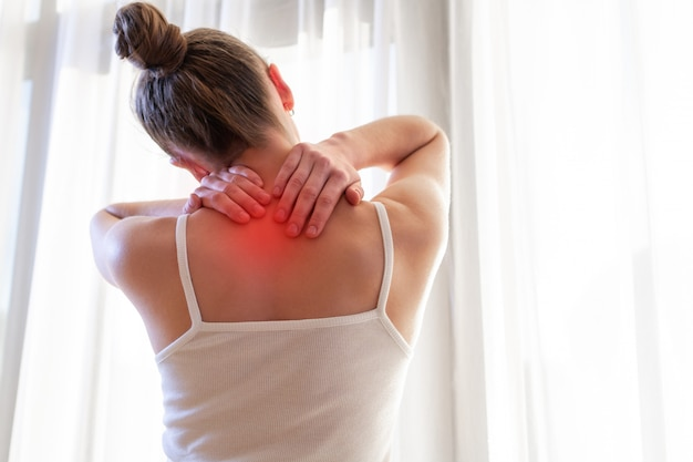 Mujer joven masajeando su cuello por sufrir dolor en el cuello, estirando los músculos.