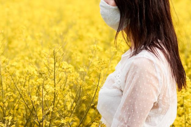 Mujer joven con máscara en un campo con flores de violación