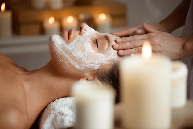 Mujer joven en la máscara para la cara relajante en el salón de spa.