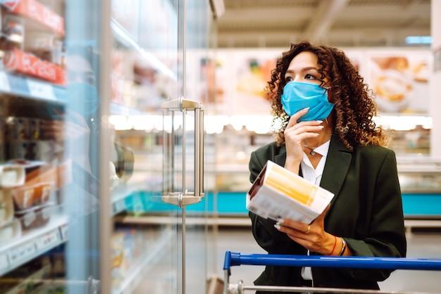 Mujer joven con máscara comprando en el supermercado. compras durante la pandemia.