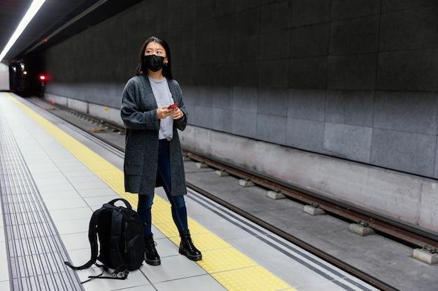Mujer joven con máscara en la estación de metro