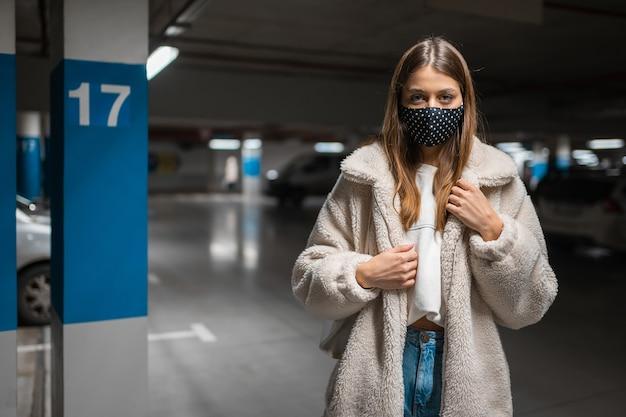 Mujer joven en máscara en el estacionamiento subterráneo