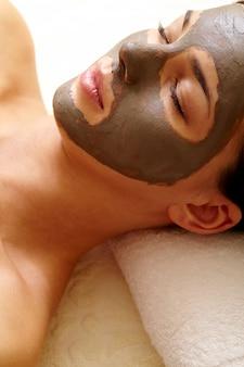 Mujer joven con máscara facial de arcilla