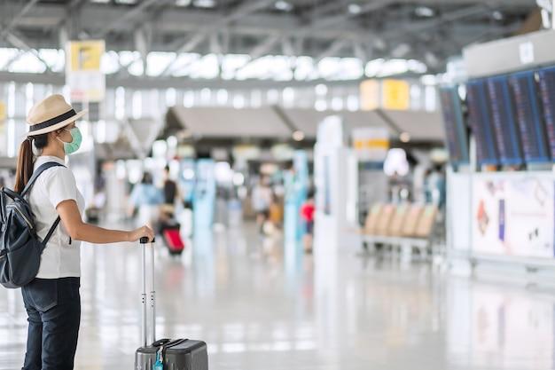 Mujer joven con máscara facial con equipaje comprobando el tiempo de vuelo en el aeropuerto, protección contra la infección por coronavirus (covid-19), mujer asiática viajera con sombrero. nuevo concepto de burbuja de viaje y normal