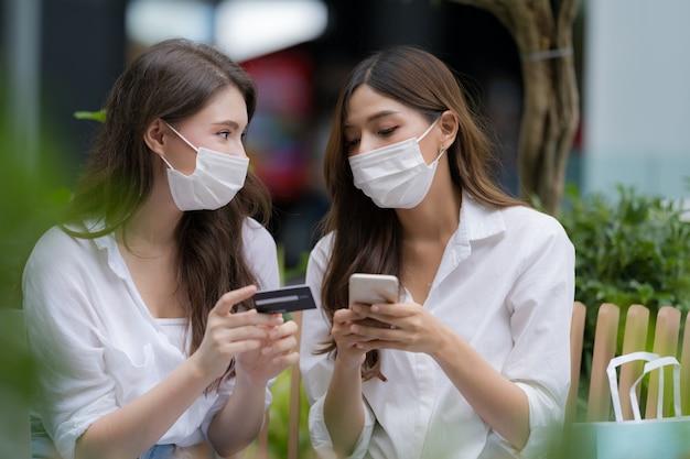 Mujer joven con máscara facial protectora hablando y riendo sosteniendo una tarjeta de crédito