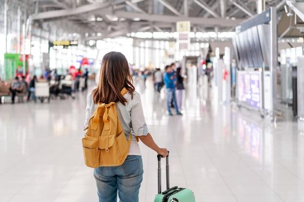 Mujer joven con una máscara facial y sosteniendo un teléfono móvil está buscando un mostrador de facturación en el aeropuerto