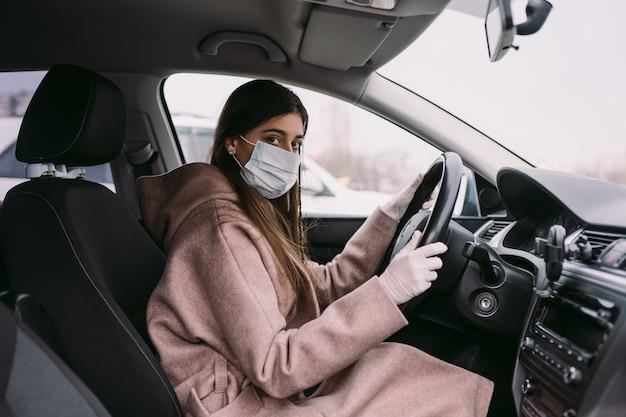 Mujer joven con una máscara y guantes conduciendo un coche.