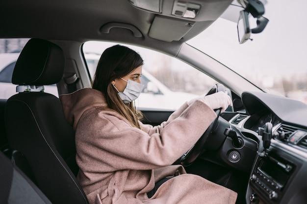 Mujer joven en una máscara y guantes de conducir un coche.