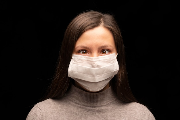 Una mujer joven con una máscara médica blanca del coronavirus simula estrabismo. ignora y se ríe de la infección viral, falsa y rara. retrato de primer plano