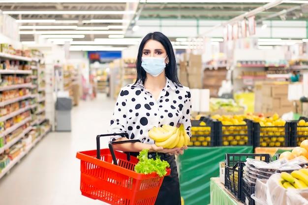 Mujer joven en una máscara médica desechable está comprando en el supermercado