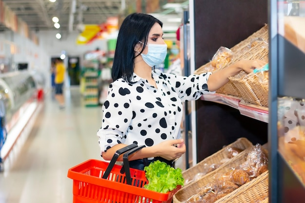 Mujer joven con máscara médica desechable de compras en el supermercado durante el brote de neumonía por coronavirus. medidas de protección y prevención en tiempo de epidemia.