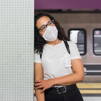 Mujer joven con máscara médica esperando