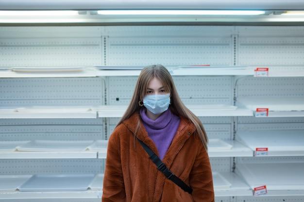 Mujer joven en máscara médica y estantes vacíos en supermercado