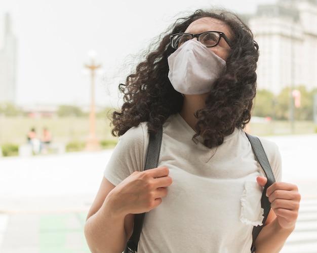 Mujer joven con una máscara médica mientras mira hacia arriba