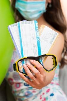 Mujer joven con una máscara médica mientras sostiene boletos de avión y gafas de buceo