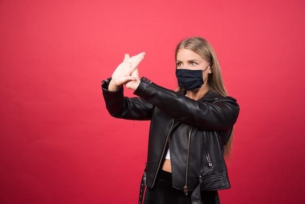 Mujer joven en máscara médica de pie y cruzando las manos haciendo señal negativa de rechazo