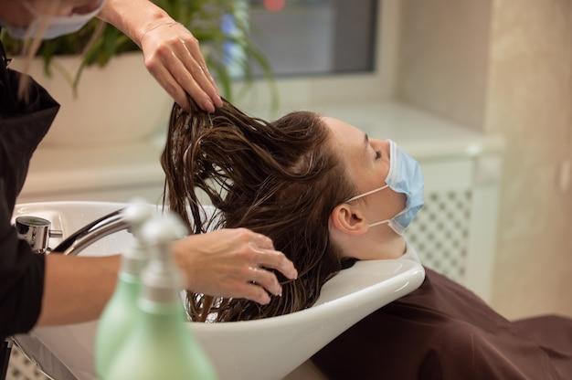 Mujer joven con máscara médica protectora obteniendo un lavado de cabello en un salón de belleza durante la pandemia
