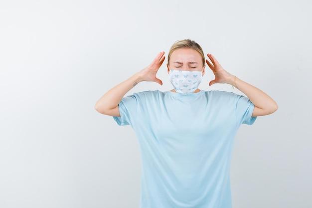 Mujer joven con una máscara médica que tiene dolor de cabeza