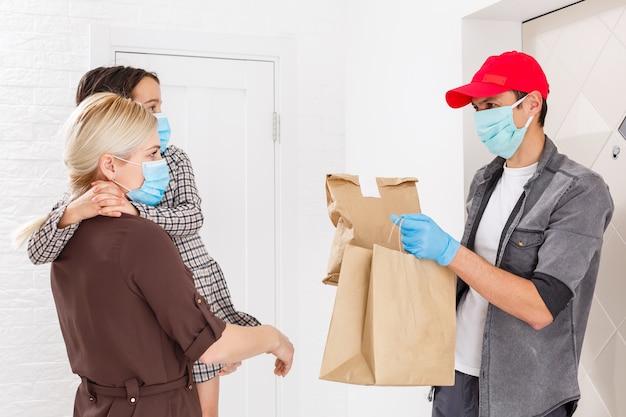 Mujer joven con máscara médica recibiendo comida ordenada del restaurante del repartidor en el interior. prevención de la propagación del virus.