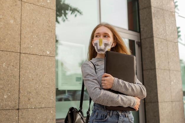 Mujer joven con máscara médica sosteniendo su portátil fuera
