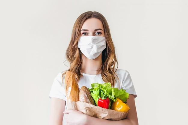 Mujer joven en máscara médica sostiene una bolsa de papel ecológica con alimentos, frutas y verduras, pimienta, baguette, lechuga, entrega inteligente en línea segura, coronovirus, cuarentena, pandemia, concepto de quedarse en casa