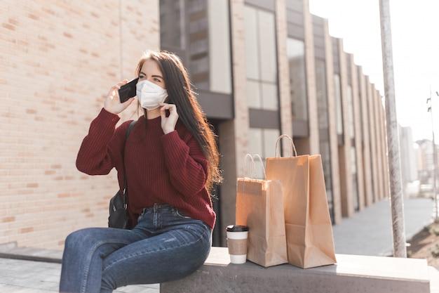 Mujer joven en máscara médica con una taza de café y bolsas