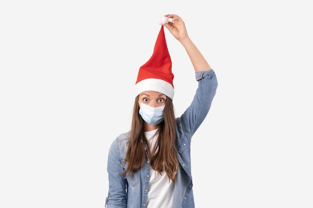 Mujer joven con máscara médica de teléfono y sombrero de santa. compras navideñas online en cuarentena. foto de alta calidad