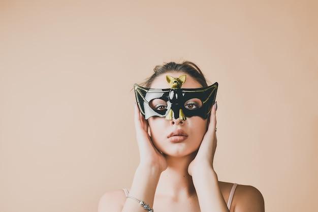 Mujer joven con una máscara de murciélago para mascarada o fiesta de halloween.