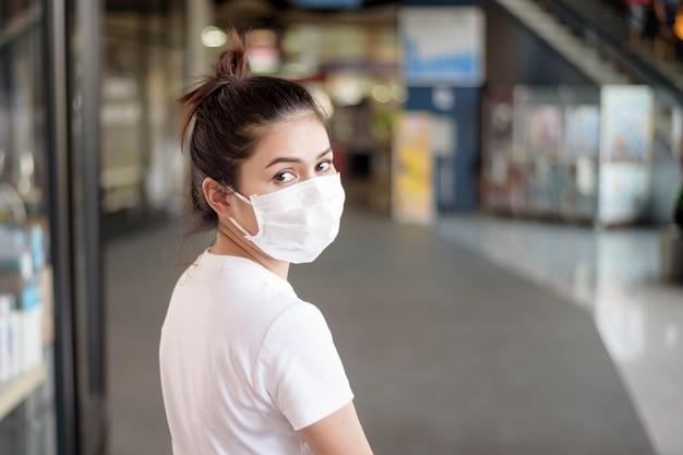 Mujer joven con máscara de pie al aire libre