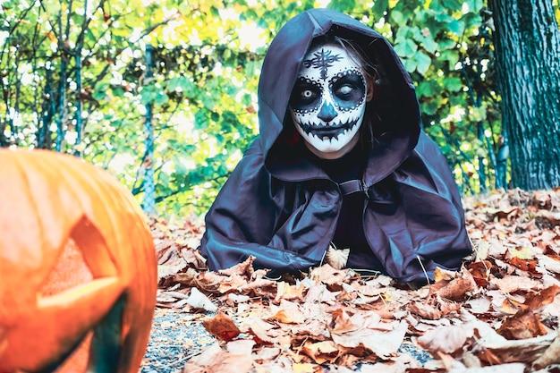 Mujer joven con máscara de pintura de halloween vistiendo capucha negra