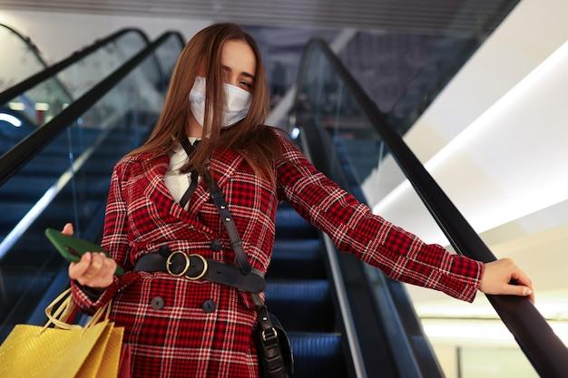 Una mujer joven con una máscara protectora después de ir de compras sube la escalera mecánica