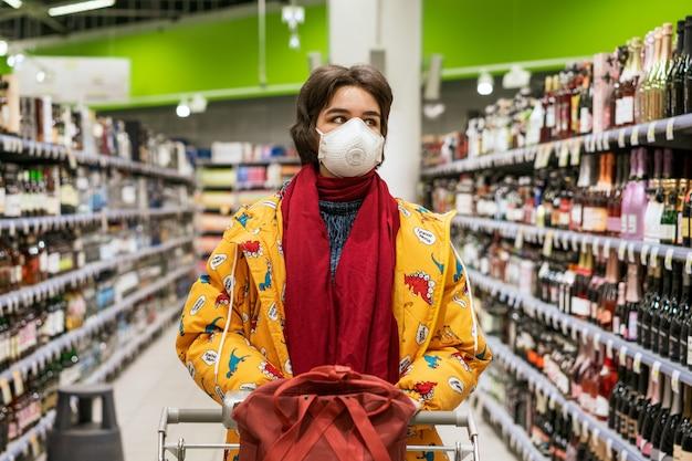 Mujer joven con una máscara protectora elige alcohol en un supermercado, las acciones se ponen en cuarentena