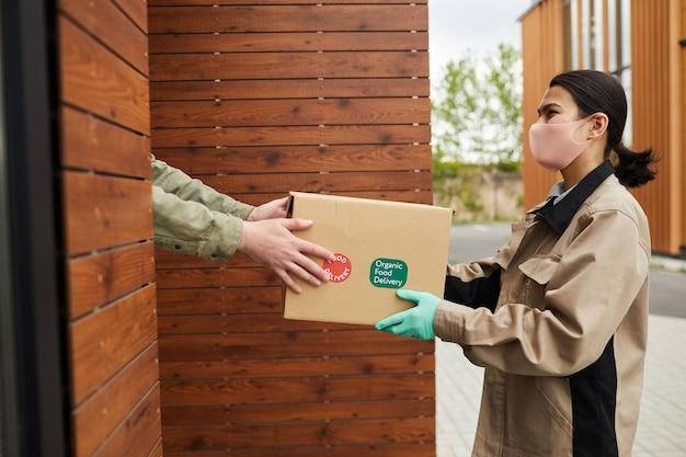Mujer joven con máscara protectora y guantes pasando la caja al cliente ella de pie al aire libre y entregando el paquete
