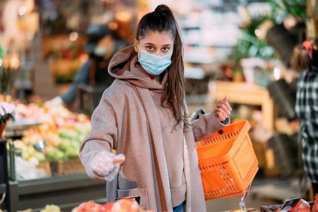 Mujer joven con máscara protectora hace compras en el supermercado