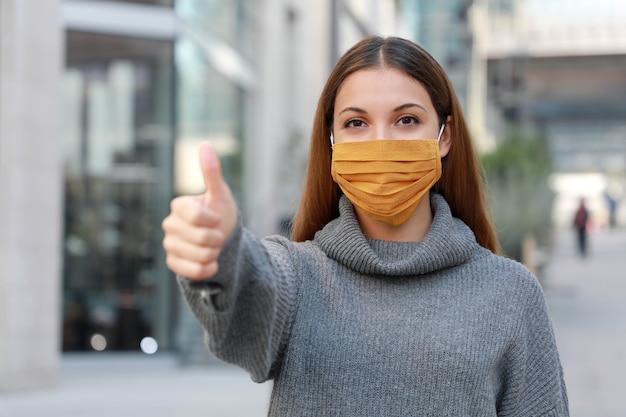 Mujer joven con máscara protectora mostrando los pulgares para arriba