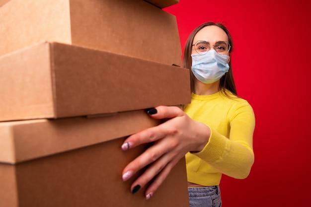 Una mujer joven con una máscara protectora tiene cajas de cartón para moverse sobre un fondo rojo.