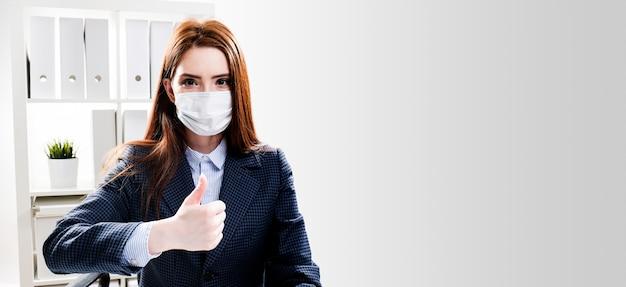 Una mujer joven con una máscara protectora trabaja en una computadora. mujer de negocios en una máscara médica en la oficina.