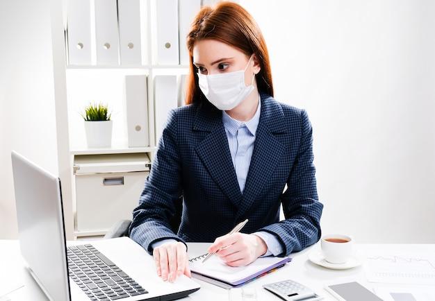 Una mujer joven con una máscara protectora trabaja en una computadora.