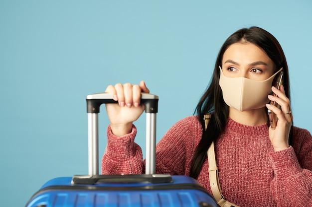 Mujer joven con máscara protectora de virus y hablando por teléfono móvil mientras espera vuelo sobre fondo azul. copie el espacio. concepto de viaje, coronavirus.