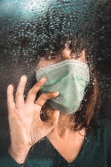 Una mujer joven con una máscara puso en cuarentena la pandemia de covid-19 en la ventana en un día lluvioso