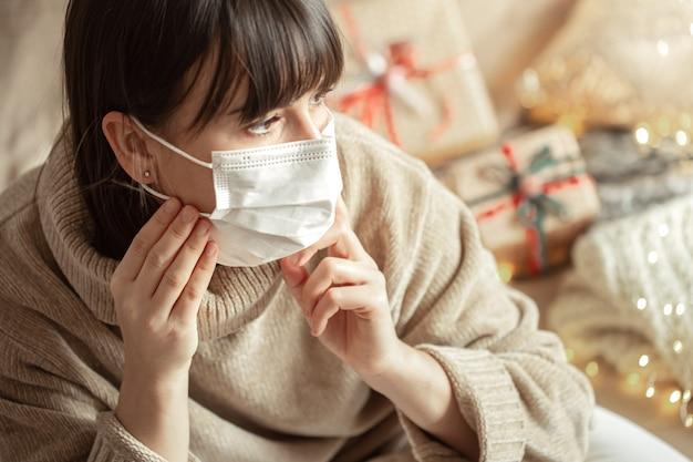 Mujer joven con máscara en el rostro en un acogedor suéter beige