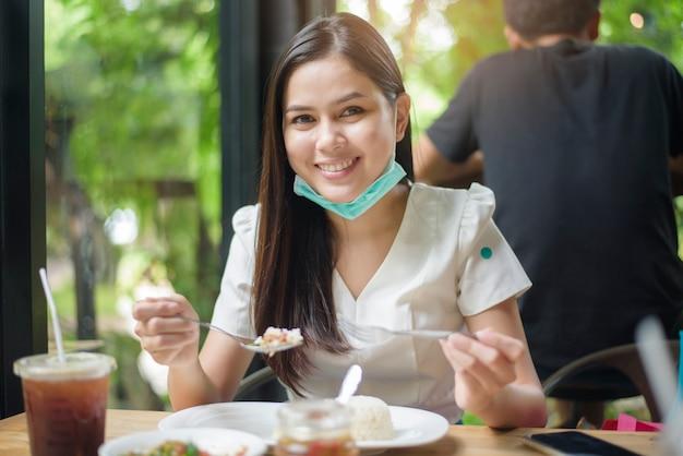 La mujer joven con la mascarilla está comiendo en el restaurante, nuevo concepto normal.