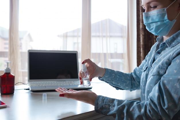 Mujer joven en mascarilla desinfectando superficies de aparatos en su lugar de trabajo