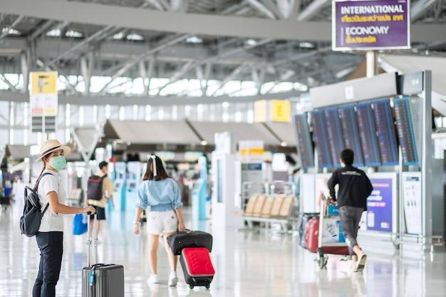 Mujer joven con mascarilla con equipaje caminando en la terminal del aeropuerto, protección contra la infección por coronavirus (covid-19), viajera asiática con sombrero. nuevo concepto de burbuja de viaje y normal