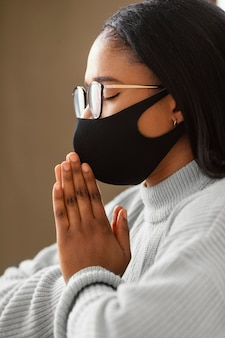 Mujer joven con una mascarilla mientras rezaba