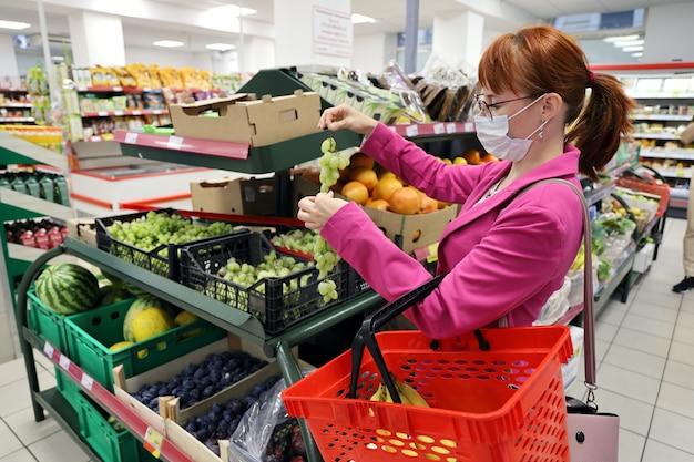 Mujer joven con mascarilla protectora, sosteniendo racimos de uvas en el supermercado
