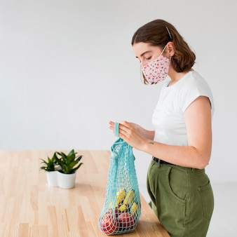 Mujer joven con mascarilla sacando comestibles de la bolsa