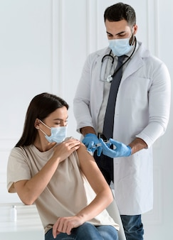 Mujer joven con mascarilla siendo vacunada por médico