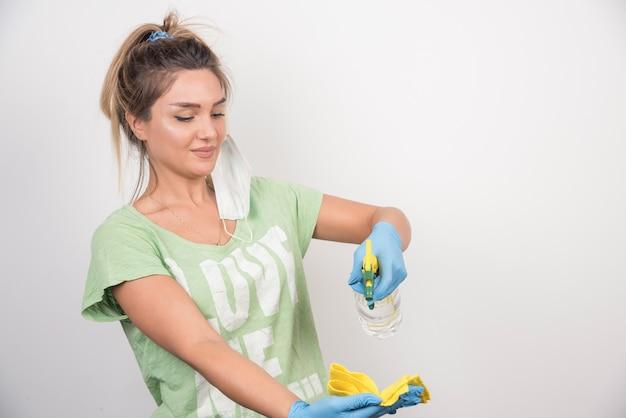 Mujer joven con mascarilla y suministros de limpieza.
